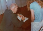 "Frank Stanger signing ""A Celebration of Ministry"" [ca 1982]"