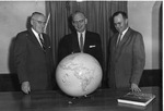 Frank Stanger with W C Mavis and W E Savage looking at a globe.