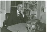 J. C. McPheeters posing in office using a Dictaphone