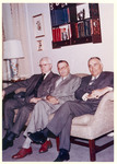J.C McPheeters siting on a couch next to two unidenfied men