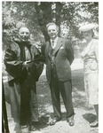 J.C McPheeters in academic dress and standing next to an unidentified man and woman