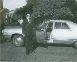 J. C. McPheeters standing beside car