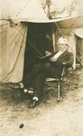 H. C. Morrison sitting outside tent with a book in hand