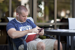 A Male Student Reading Outside the Library
