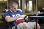 A Male Student Reading Outside the Library - 3
