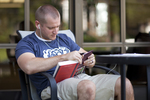 A Male Student Reading Outside the Library - 4