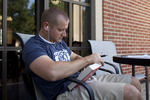 A Male Student Reading Outside the Library - 5