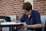 A Male Student Studying on the Library Porch