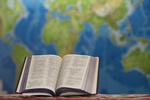 An Open Bible In Front of a Global Map