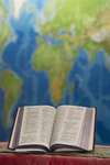 An Open Bible In Front of a Global Map - 2