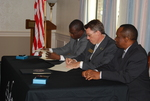 Dr. William Udotong, Dr. Tim Tennent, and Dr. Douglas Carew Signing Documents