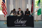 Dr. William Udotong, Dr. Tim Tennent, and Dr. Douglas Carew Signing Documents - 3