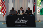 Dr. William Udotong, Dr. Tim Tennent, and Dr. Douglas Carew Signing Documents - 9