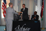 Dr. Tim Tennent Handing Documents to Dr. Leslie Andrews