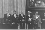 5 men seated on stage