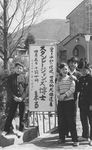 Young boys posing next to the sign announcing ESJ's visit at Kyoto Fukko